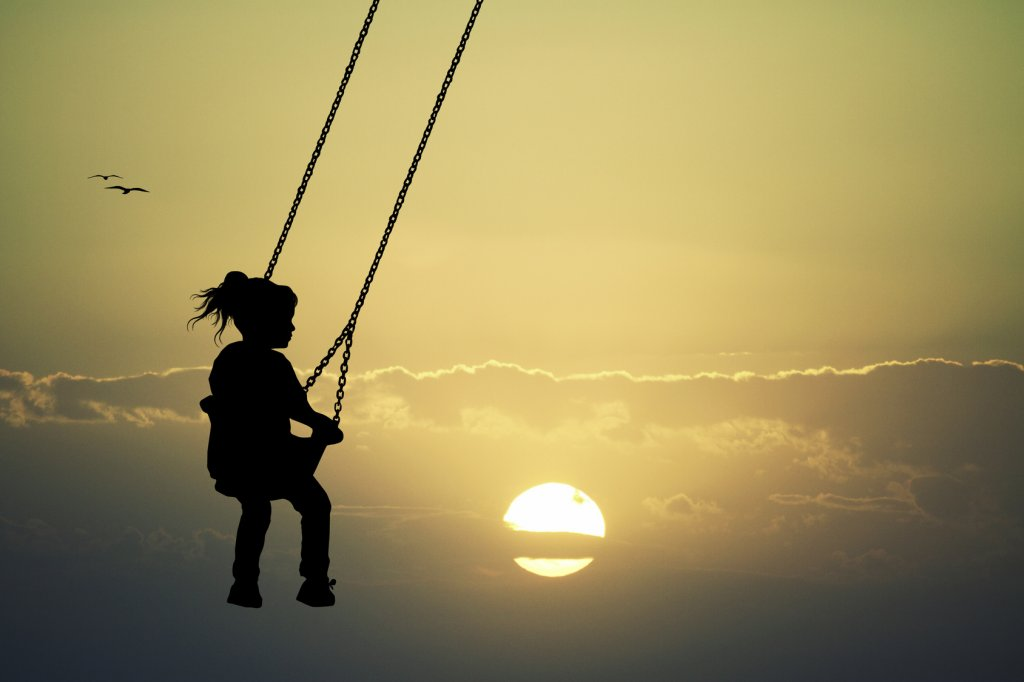 Self-Love takes care of the little girl on swing at sunset